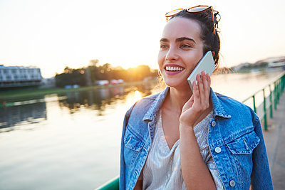 Smiling young woman on cell phone at the riverside at sunset - p300m2012232 by gpointstudio