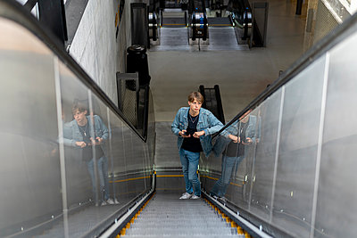 Young man with cell phone on escalator - p300m2102156 von VITTA GALLERY