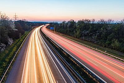 Germany, Baden-Wuerttemberg, traffic light trails on Autobahn A8 at dusk - p300m2104142 by Werner Dieterich