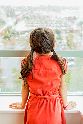 Young girl looking out the window on a rainy day; Surrey, British Columbia, Canada - p442m2091894 by Lorna Rande