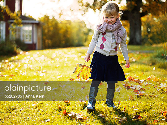 Girl holding autumn leaf and walking in garden