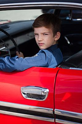 Junge am Steuer eines roten Autos, Baujahr 1959 - p045m2014790 von Jasmin Sander