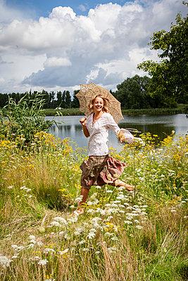 Blonde woman running through flowering meadow  - p1093m2193620 by Sven Hagolani