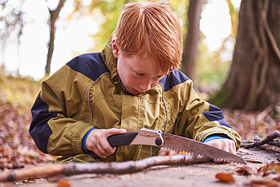Redheaded boy treating branch with bow in autumnal forest - p300m1417034 by Jess Derboven