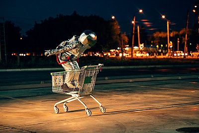 Spaceman in the city at night on parking lot inside shopping cart - p300m2043148 by Vasily Pindyurin