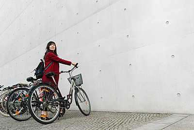Businesswoman taking bicycle in the background of modern building - p300m2155203 by Hernandez and Sorokina