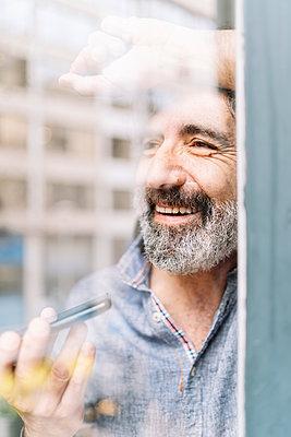 Smiling senior man talking on smart phone at home seen through glass - p300m2277133 by COROIMAGE