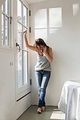Mature woman standing in part furnished home, talking on mobile phone - p429m1062321f by Jakob Valling