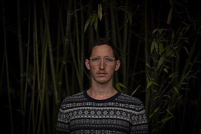 Young man wearing spectacles against bamboo plants - p552m1589958 by Leander Hopf
