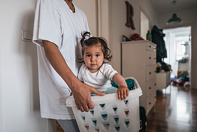 Toddler girl sitting in laundry basket - p586m1178775 by Kniel Synnatzschke