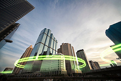 Green light trails surrounding skyscrapers - p924m806958f by Bjorn Holland