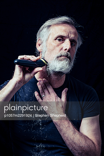 A middle aged man shaving off his grey beard that he grew duyring the lockdown caused by the covid-19 pandemic. - p1057m2291924 by Stephen Shepherd