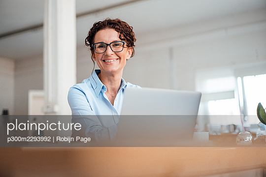Smiling businesswoman wearing eyeglasses sitting with laptop at office - p300m2293992 by Robijn Page