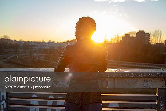 Silhouette einer jungen Frau im abendlichen Gegenlicht auf einer Brücke - p770m2081915 von mbphoto