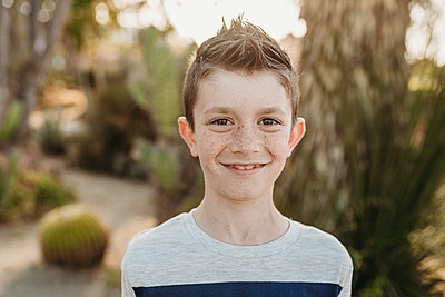 Close up portrait of cute young boy with freckles smiling outdoors - p1166m2136636 by Cavan Images