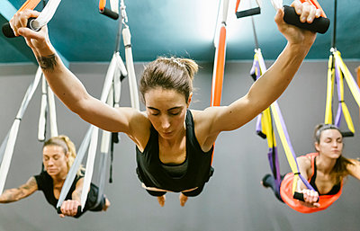 Group of women having a class of aerial yoga - p300m1416856 by Marco Govel