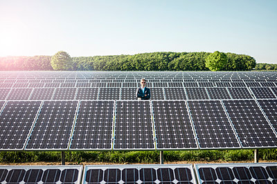 Mature man standing on panel in solar plant - p300m2005469 by Robijn Page
