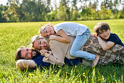 Smiling family lying on grass during sunny day - p300m2197466 by Stefanie Aumiller