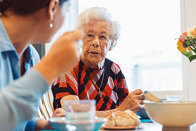 Senior woman talking to daughter while having food at home - p426m1468266 by Maskot