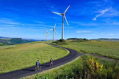 Cyclists on a countryside road with wind turbines - p813m924351 by B.Jaubert