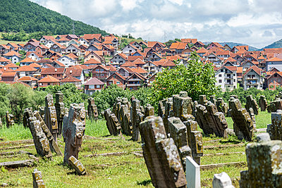 Medieval balkan tombstones in front of new terra cotta pitched-roof houses. The tombstones stand at the Serbian Orthodox Church of St. Peterin Rasa, near Novi Pazar, Serbia. - p855m1219695 by Matthew Worsnick