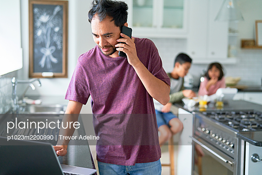 Man working at laptop in kitchen with kids - p1023m2200990 by Trevor Adeline