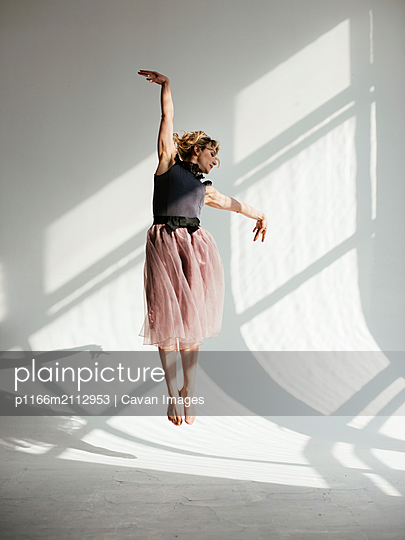 Ballerina jumping against white wall in dance studio - p1166m2112953 by Cavan Images