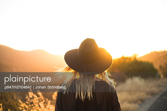 Rear View Of A Young Woman In Black Hat At Sunset   - p847m2104841 by Johan Strindberg
