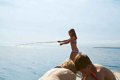 Girl in bikini fishing off sunny dock - p1023m1172717 by Francis Pictures