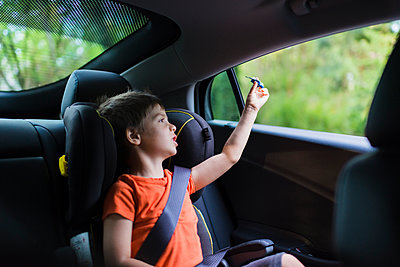 Cute boy playing with toy rocket on back seat of car - p1166m1474006 by Cavan Images