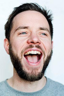 Mann lachend vor weißem Hintergrund - p177m1216913 von Kirsten Nijhof