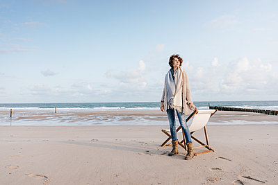 Woman standing next to deckchair on the beach - p300m1499371 by Kniel Synnatzschke