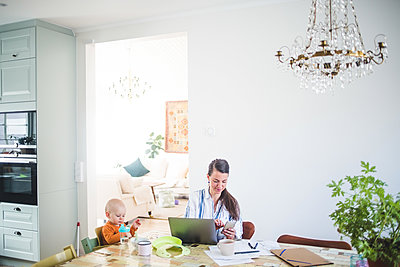 Female freelancer working while taking daughter's care at home office - p426m2117004 by Maskot