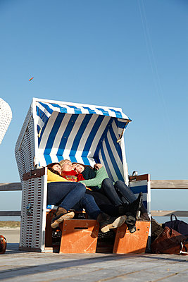 Three girls in a hooded beach chair - p981m952255 by Franke + Mans