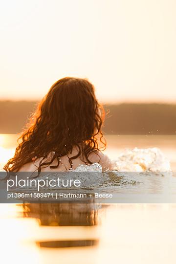 Frau badet im See in der Abendsonne - p1396m1589471 von Hartmann + Beese