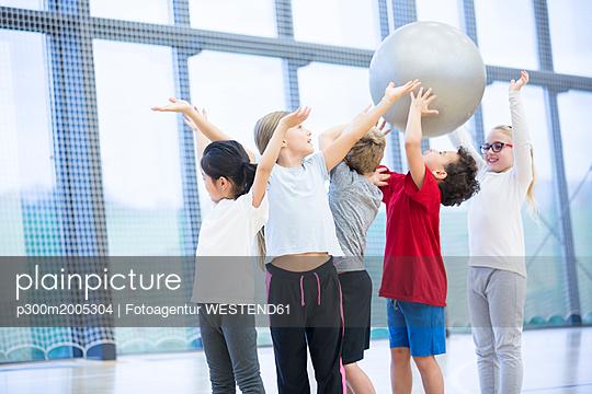 Pupils handing over gym ball in gym class - p300m2005304 von Fotoagentur WESTEND61