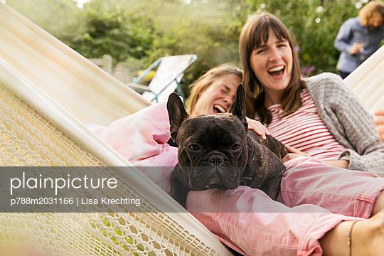 Zwei Frauen mit Hund in einer Hängematte - p788m2031166 von Lisa Krechting