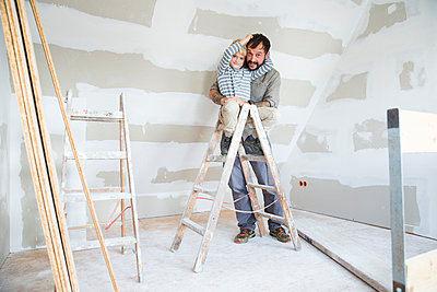 Portrait of happy father and son working on loft conversion - p300m2083759 by Michelle Fraikin