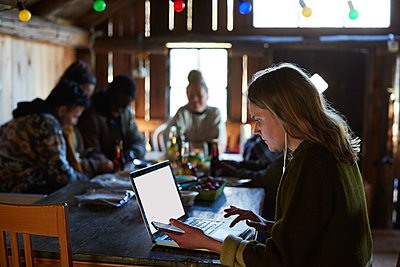 Young woman using laptop on table while friends talking in background at log cabin - p426m2117249 by Maskot