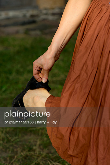 Junge Frau zieht ihre Sandale an - p1212m1159153 von harry + lidy