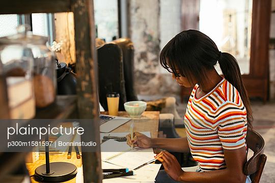 Young woman working at desk in a loft - p300m1581597 von Bonninstudio