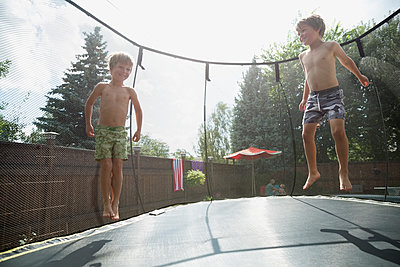 Bare chested boys jumping on trampoline in sunny backyard - p1192m1184061 by Hero Images