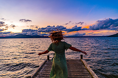 Woman on boardwalk at sunrise, New Zealand - p1455m2204881 by Ingmar Wein