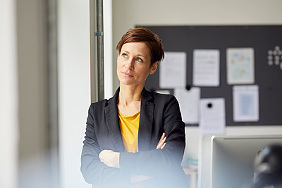 Attractive businesswoman standing in office with arms crossed - p300m2013002 von Rainer Berg
