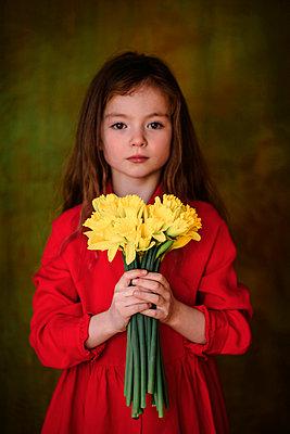 Portrait of little girl in red dress with bunch of daffodils - p300m2121803 von Oxana Guryanova