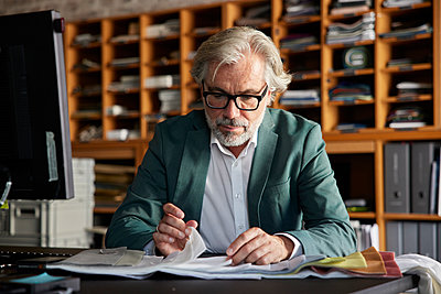 Male design professional choosing fabric from swatch at desk in office - p300m2299898 by Rainer Berg