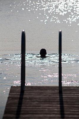 Man swimming in lake - p817m2016133 by Daniel K Schweitzer