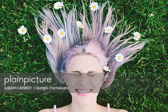 Portrait of woman lying on grass with eyes closed and daisies on hair - p300m1469831 by Giorgio Fochesato