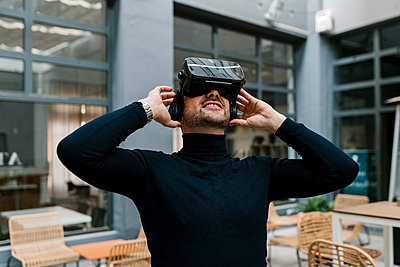 Smiling businessman using virtual reality headset while sitting at cafe - p300m2265838 by Ezequiel Giménez