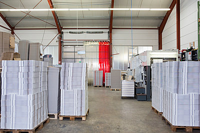 Stacked cardboard stock on pallets in warehouse - p429m942786f by Judith Haeusler